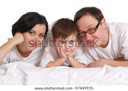Family of three in white shirts on the bed on a white background