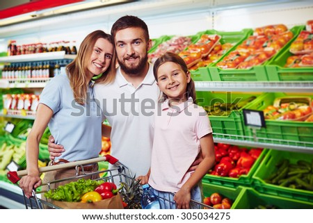 Family of three looking at camera in supermarket - stock photo