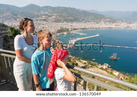Family of three looking at the beautiful view of the sea from the hill - stock photo