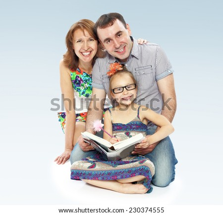 Family of three mom dad and daughter reading a book. - stock photo