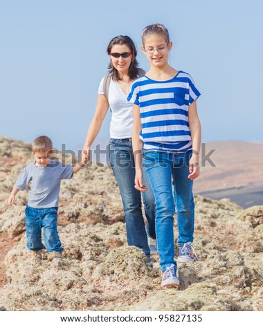 Family of three - mother and her child hiking in the cross-country - stock photo