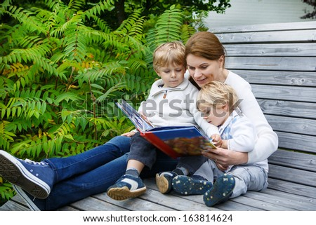 Family of three (mother and two sibling boys) sitting on bench in park and reading fairytale book together.