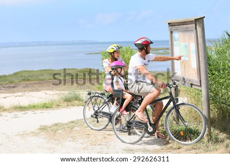 Family of three on a biking day looking at map - stock photo