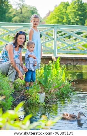 Family of three on a walk in the park watching the ducks - stock photo