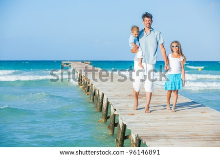 Family of three on wooden jetty by the ocean - stock photo
