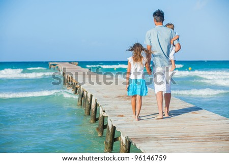 Family of three on wooden jetty by the ocean. Back view - stock photo