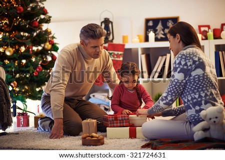 Family of three packing gifts and tying knots on tops of boxes before Christmas - stock photo