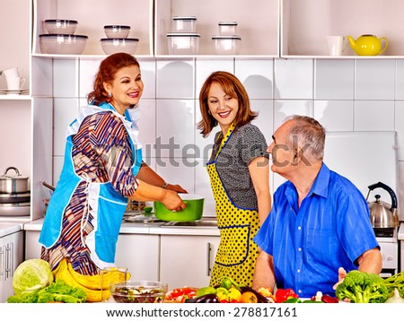 family of three people cooking at kitchen. Grandfather and grandmother with his adult daughte - stock photo
