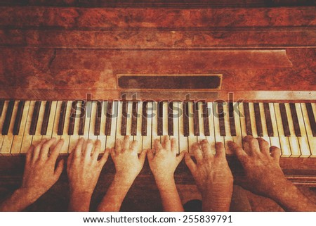 Family of three people is playing the piano, front view. Point of view shot. Vintage image - stock photo