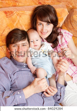 Family of three people lying down at bed, cuddling and smiling. High angle view - stock photo