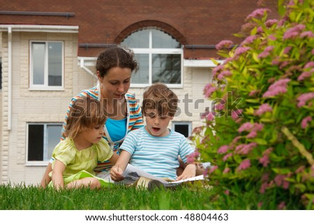 Family of three people on lawn in front of house. Mother with her daughter and son see paper. - stock photo
