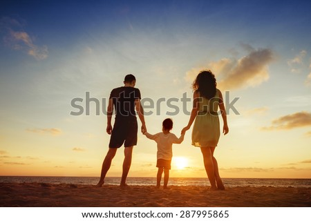 Family of three person is standing on sunset and sea backdrop - stock photo