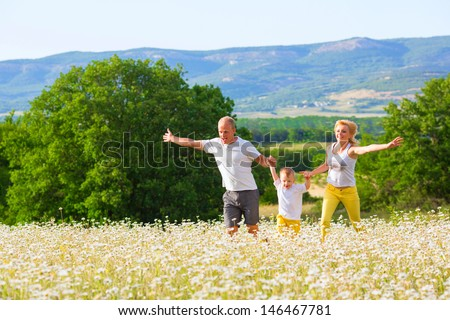 Family of three person on the camomile meadow