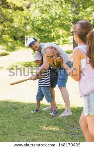 Family of three playing baseball in the park - stock photo