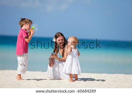 Family of three playing on tropical beach and making soap bubbles - stock photo
