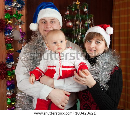 Family of three posing for  Christmas portrait at home