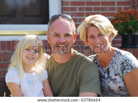 family of three posing in front of home - stock photo