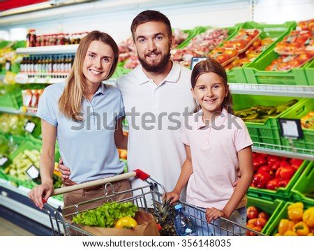 Family of three shopping in grocery supermarket