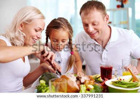Family of three sitting at the table and going to eat roasted turkey - stock photo