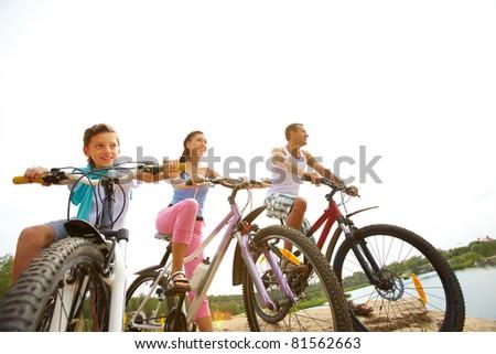 Family of three sitting on bikes - stock photo
