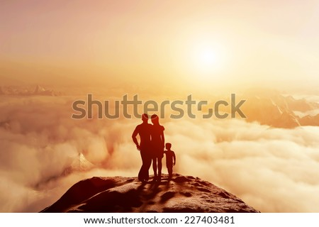 Family of three standing together on mountain and looking on cloudscape horizon at sunset. Parents and child, conceptual. - stock photo