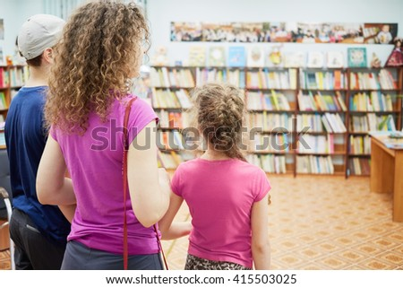 Family of three stands at room with bookcases full of books in library.