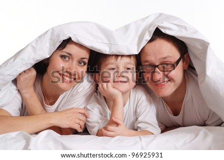 Family of three under a blanket on the bed