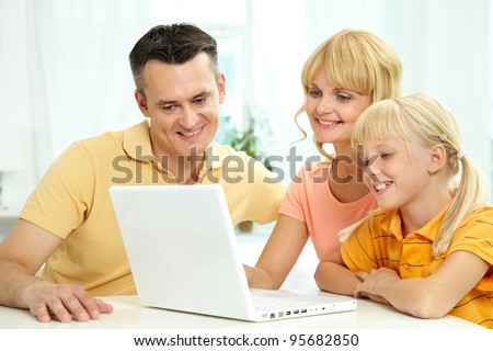 Family of three using laptop together
