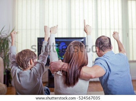 Family of three watching sports on TV and cheering with raised arms. Rear view.