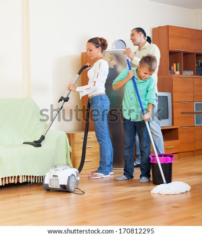 Family of three with teenager vacuuming together at home