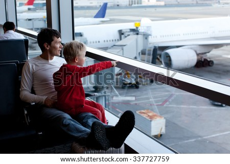 family of two at the airport enjoying time together before airplane departure - stock photo