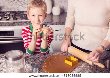 family of two baking gingerbread cookies at home at christmas time, holiday concept