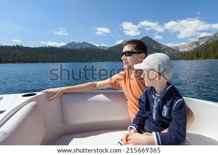family of two enjoying boat ride at lake tahoe, california/nevada state - stock photo