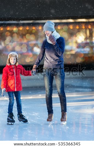 family of two enjoying ice skating at winter at outdoor skating rink at snowy weather, winter and family concept