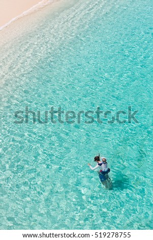 family of two enjoying snorkeling at caribbean vacation, active and healthy lifestyle with copyspace