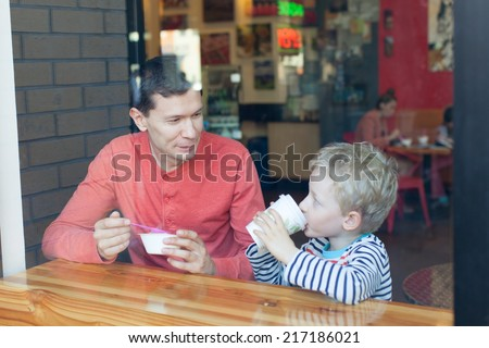 family of two enjoying their day together in cafe - stock photo