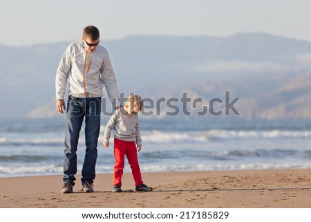 family of two having fun at the beach in california - stock photo