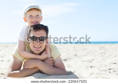 family of two having fun at the beach together at summer - stock photo
