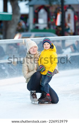 family of two having fun ice skating together at winter - stock photo