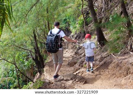 family of two hiking together the kalalau trail at kauai island, hawaii - stock photo