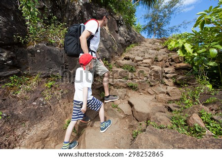 family of two hiking up together the strenuous kalalau trail along na pali coast of the island of kauai in the state of hawaii, spending active time together at vacation - stock photo