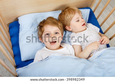 Family of two little brothers: little boys having fun in bed at home, indoors. Kids, sbilings twins playing together. Carefree childhood and sibling love concept. - stock photo