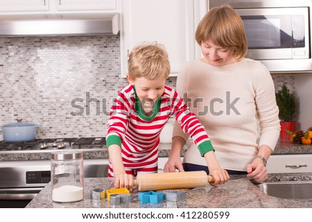 family of two, mother and son, being cozy at home at christmas time and making gingerbread cookies together - stock photo