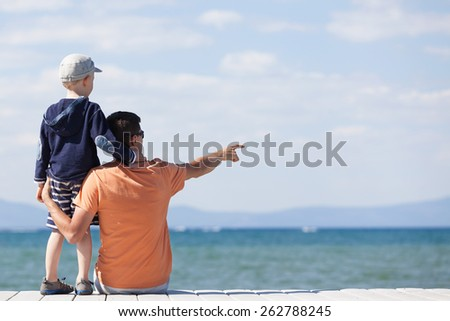family of two sitting at the dock at the lake - stock photo