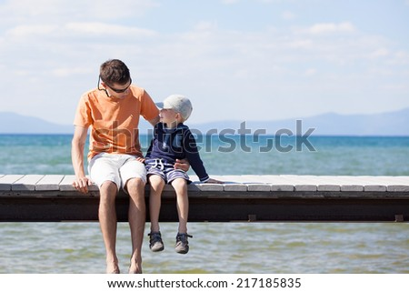family of two sitting at the dock together at summer - stock photo