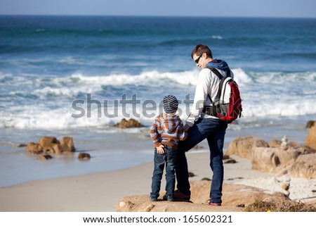 family of two spending time together by the ocean and enjoying the view - stock photo