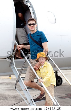 family of two standing at the airstairs ready to get in the plane  - stock photo