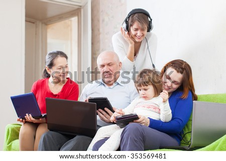 family of with various PC on sofa at home