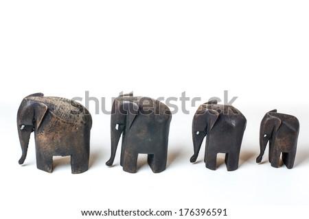 Family of wooden elephants on white background - stock photo