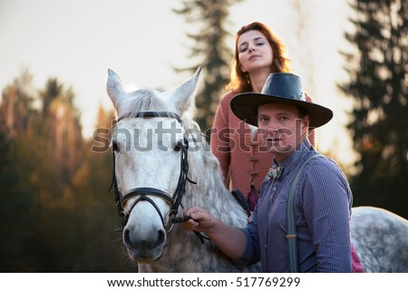 Family of young farmers, a man in a shirt and a cowboy hat, a girl on horseback in a knitted cardigan